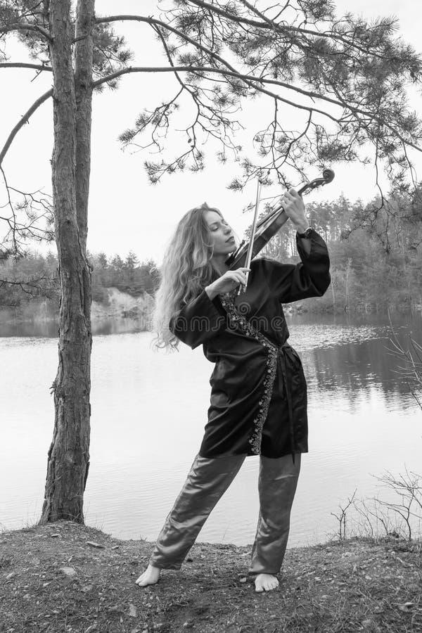 Piękna młoda dziewczyna bawić się skrzypce na brzeg jezioro fotografia royalty free