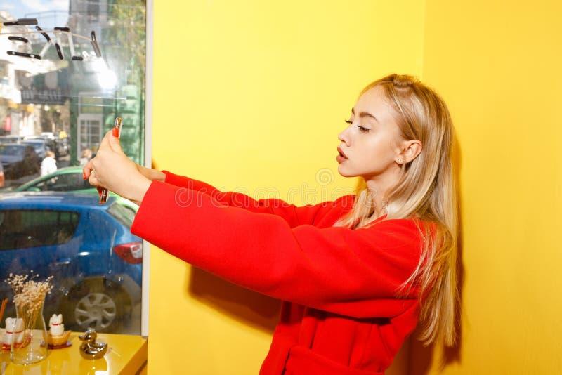 Piękna młoda dziewczyna bierze selfie na jej smartphone na tle kolor żółty blogger ubierał w eleganckim czerwonym żakiecie fotografia royalty free