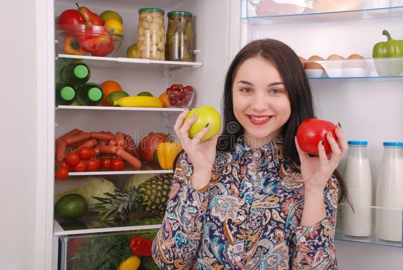Piękna młoda dziewczyna blisko Fridge z zdrowym jedzeniem obraz stock