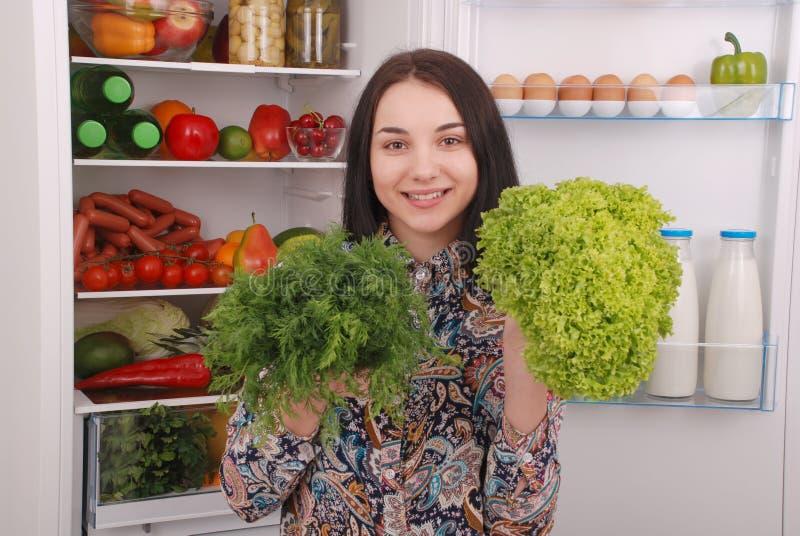 Piękna młoda dziewczyna blisko Fridge z zdrowym jedzeniem fotografia royalty free