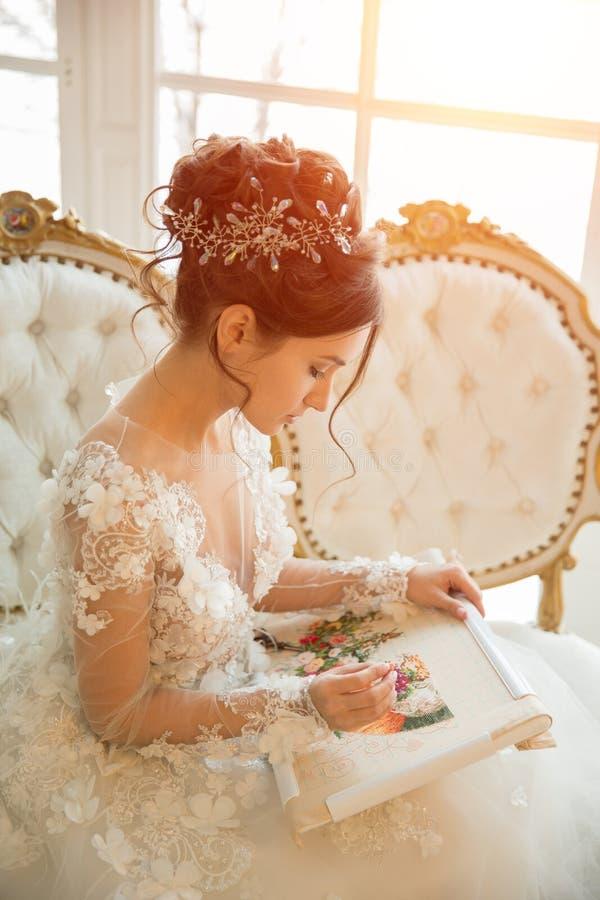 Piękna młoda dziewczyna haftuje jaskrawego pięknego wnętrze t zdjęcia royalty free