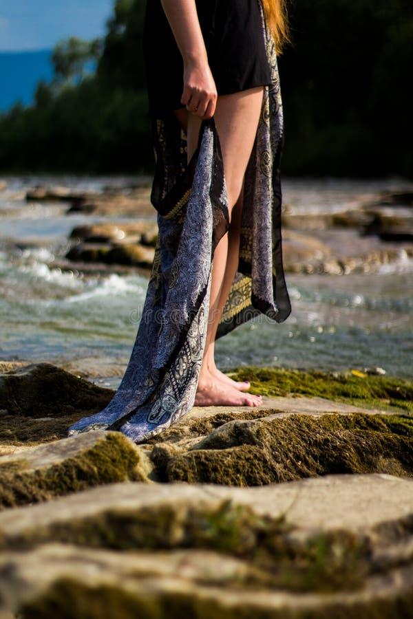 Piękna młoda dziewczyna na skale blisko rzeki fotografia stock