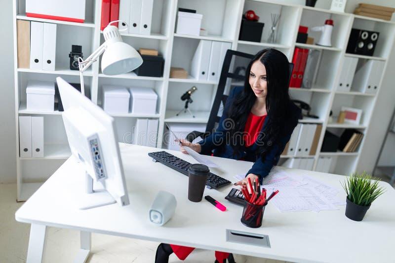 Piękna młoda dziewczyna pracuje z dokumentami komputer i kalkulator siedzi przy stołem, na krześle w biurze zdjęcie royalty free