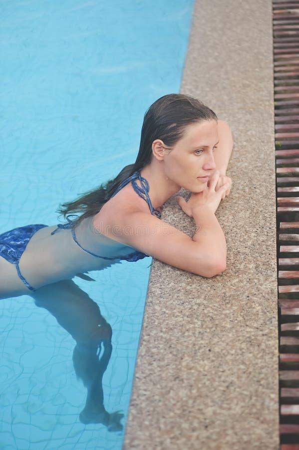 Piękna młoda dziewczyna siedzi i relaksujący w błękitnym basenie zdjęcie royalty free