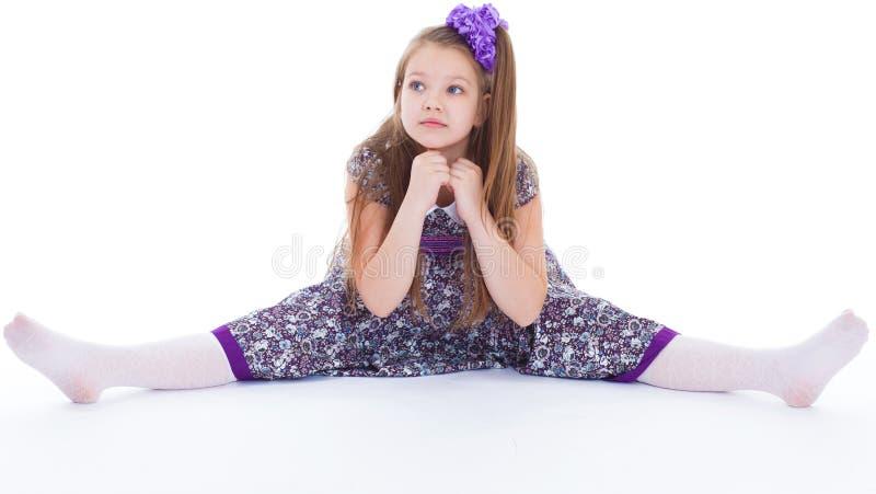 Piękna młoda dziewczyna siedzi na dratwie. obraz stock