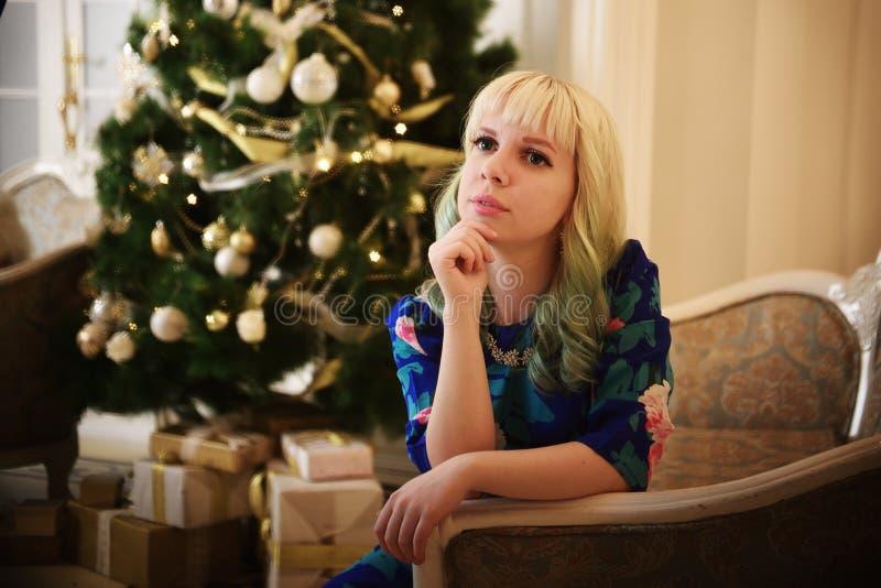 Piękna młoda dziewczyna siedzi na kanapie blisko choinki z teraźniejszość i marzy zdjęcie royalty free