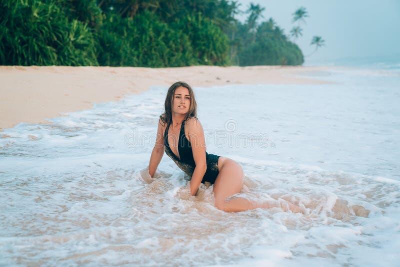Piękna młoda dziewczyna siedzi na seashore, ona zakrywał piankowatą błękit fala Model cieszy się zabawę i ma obrazy stock