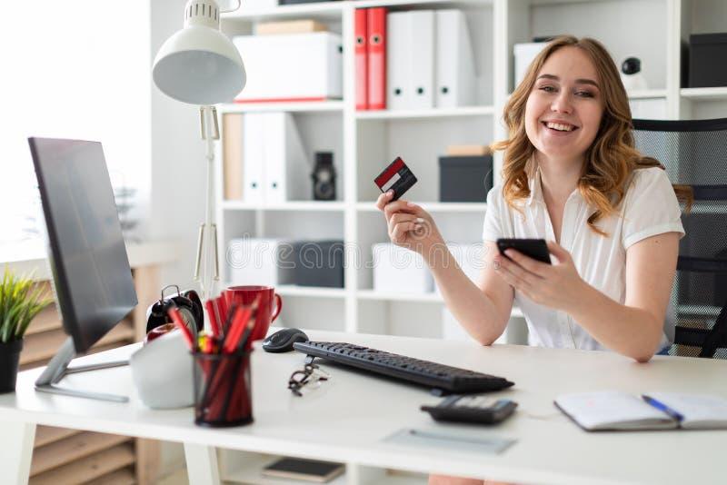 Piękna młoda dziewczyna siedzi w biurze, trzyma, bank kartę telefon w jej ręce i zdjęcia royalty free