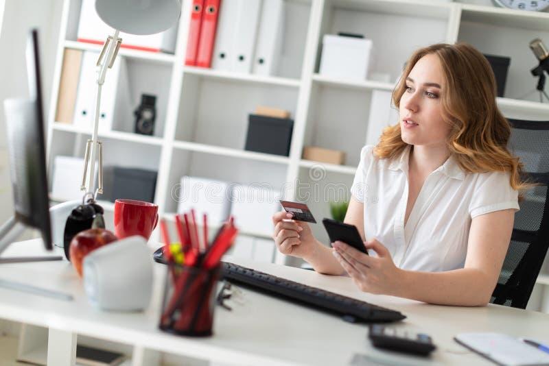 Piękna młoda dziewczyna siedzi w biurze, trzyma, bank kartę telefon w jej ręce i obrazy royalty free