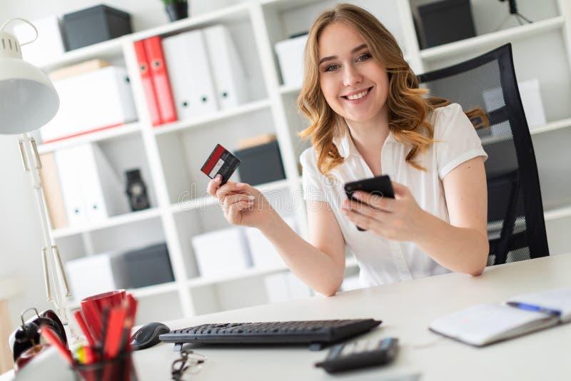 Piękna młoda dziewczyna siedzi w biurze, trzyma, bank kartę telefon w jej ręce i fotografia royalty free