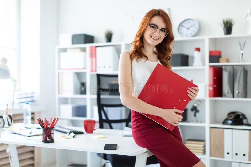 Piękna młoda dziewczyna siedział puszek na stole w biurze i trzymał czerwoną falcówkę obrazy royalty free