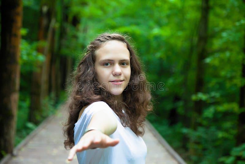 Pi?kna m?oda dziewczyna, trzyma jej r?k? za kamerze portret w lasowym Naturalnym lata tle fotografia royalty free