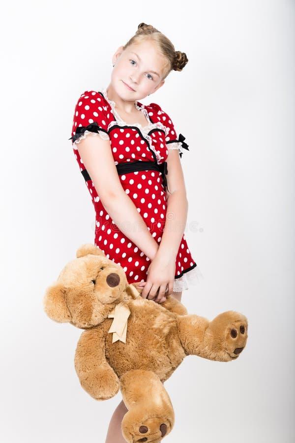 Piękna młoda dziewczyna trzyma misia ubierał w czerwonej sukni z białymi polek kropkami obraz stock