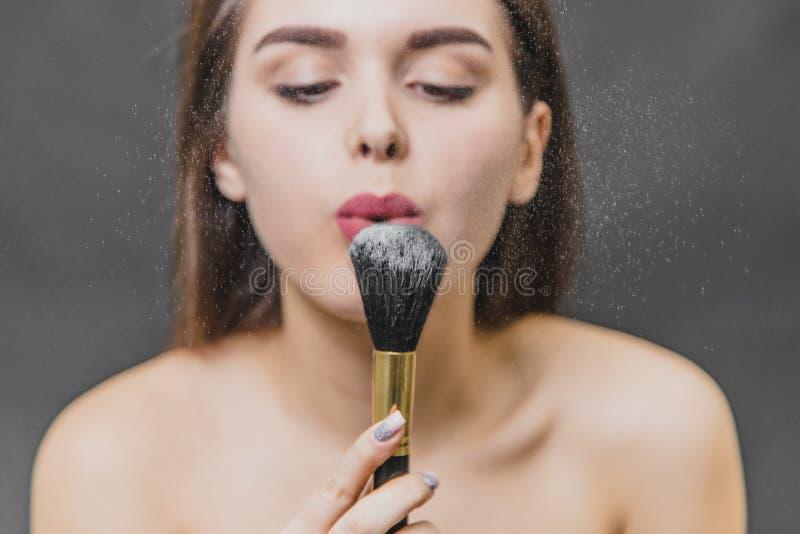 Piękna młoda dziewczyna trzyma muśnięcie dla makeup w ona ręki Ja dmucha z proszka dla makeup i spojrzeń przy nim makeup obraz stock