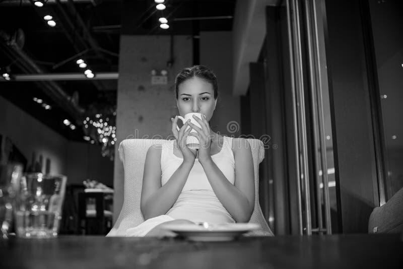 Piękna młoda dziewczyna w biel sukni z białą filiżanką siedzi w miastowej rocznik kawiarni i czułość pensively pije kawę zdjęcie stock