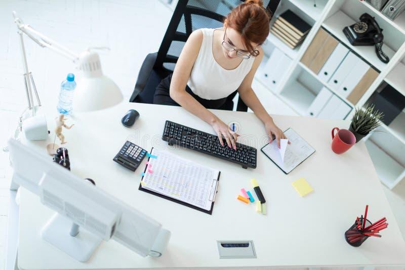 Piękna młoda dziewczyna w biurowym działaniu z dokumentami, kalkulatorem, notepad i komputerem, zdjęcia stock