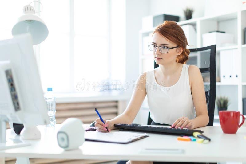 Piękna młoda dziewczyna w biurowym działaniu z piórem, dokumentami i komputerem, zdjęcia royalty free