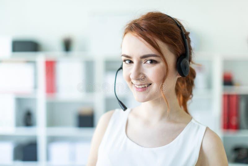 Piękna młoda dziewczyna w hełmofonach z mikrofon pozycją w biurze fotografia royalty free