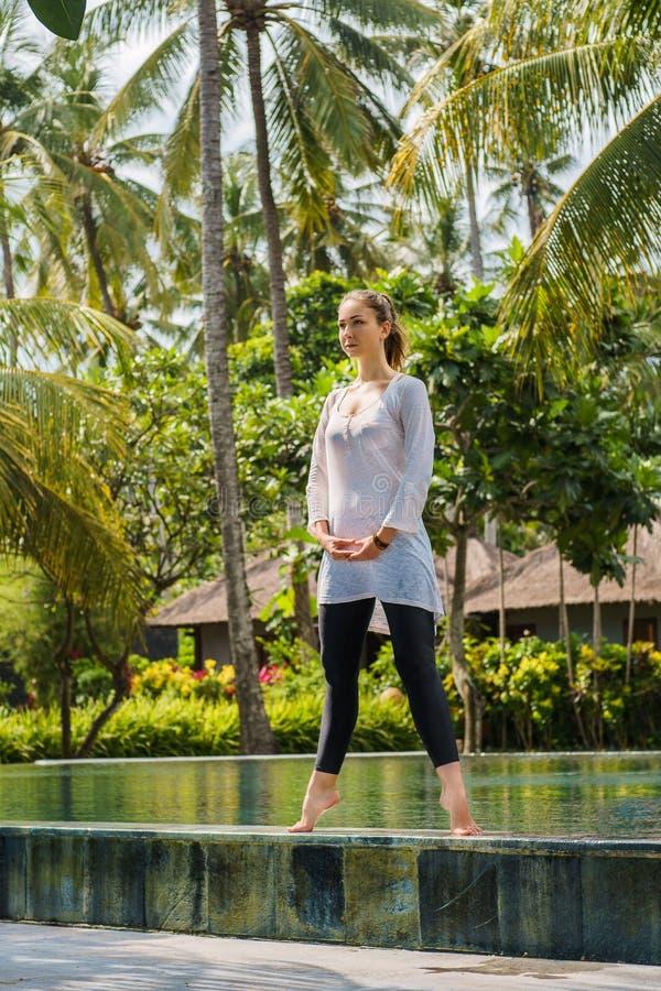 Piękna młoda dziewczyna w joga odzieży ćwiczy joga, medytacja, stoi na basenie w kurorcie w Indonezja obrazy stock