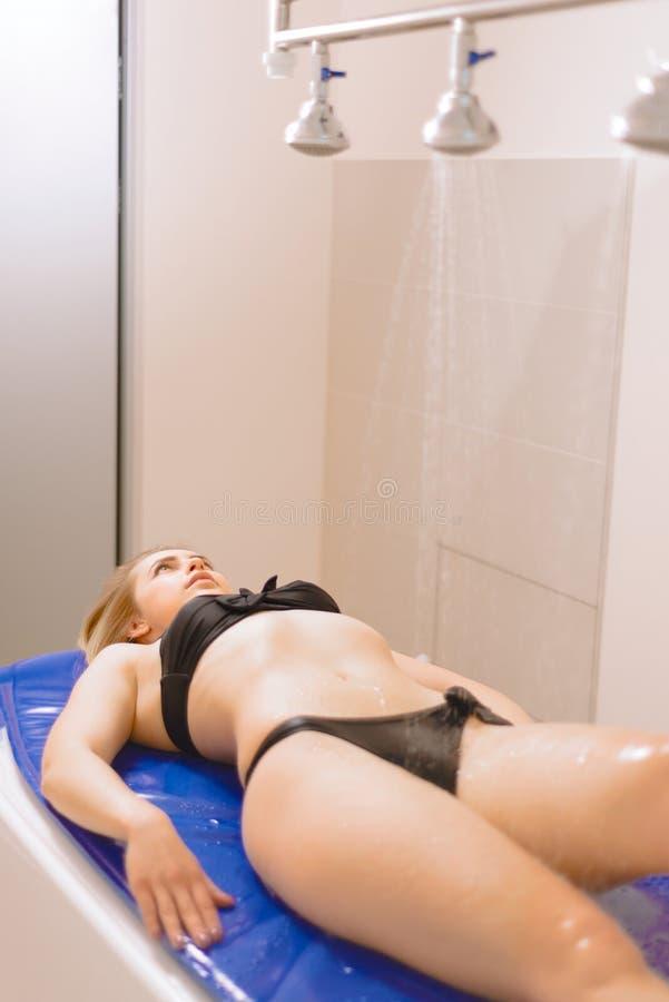 Piękna młoda dziewczyna w kostiumu kąpielowym bierze Vichy prysznic jasnego dzie? cieki kwitn? frangipani ?wie?ego chlapn?? zdr?j obrazy royalty free