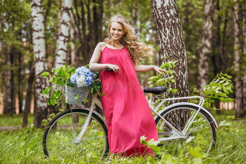 Piękna młoda dziewczyna w lato sukni przy zmierzchem Mody fotografia w lasowym modelu na bicyklu z kwiatu bukietem w menchii l, obraz stock