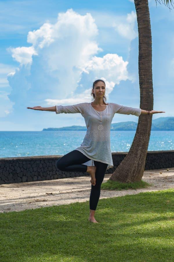 Piękna młoda dziewczyna w leggings i tunice robi joga praktyce, medytacja, tanding pozę na ocean plaży Bali Indonezja zdjęcia stock