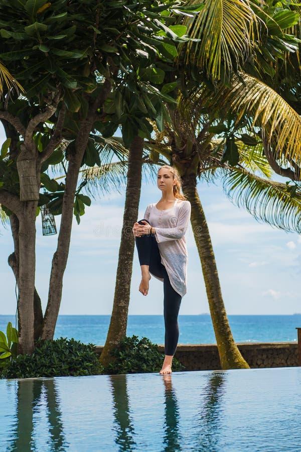 Piękna młoda dziewczyna w leggings i tunice robi joga praktyce na basenie z oceanu krajobrazem, rozciągający nogę, stoi zdjęcie royalty free