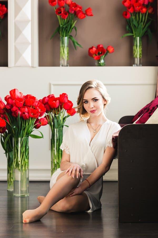Piękna młoda dziewczyna w peignoir siedzi na podłodze w studiu z bukietami tulipany zdjęcia royalty free