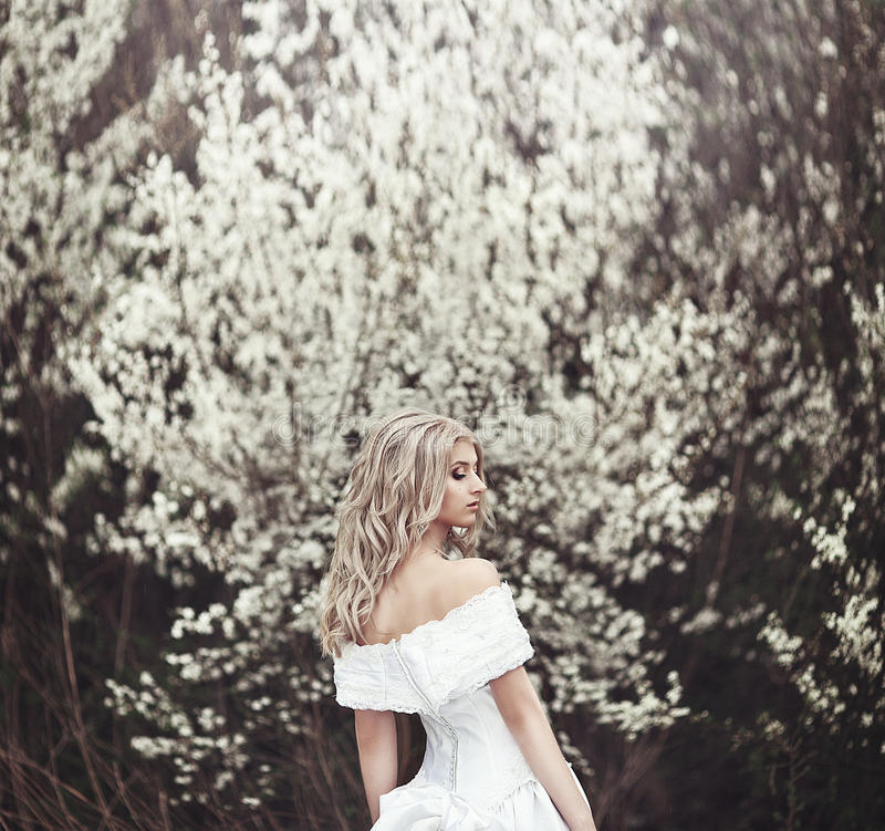 Piękna młoda dziewczyna w pięknej biel sukni blisko kwiatonośnego drzewa obraz stock
