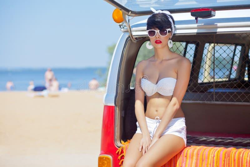 Piękna młoda dziewczyna w retro spojrzeniu z czerwonymi wargami w białym sw obraz stock