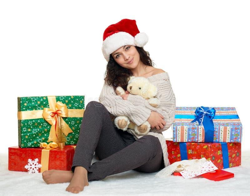 Piękna młoda dziewczyna w Santa kapeluszu z misia prezenta i zabawki pudełkami, biały tło zdjęcie royalty free