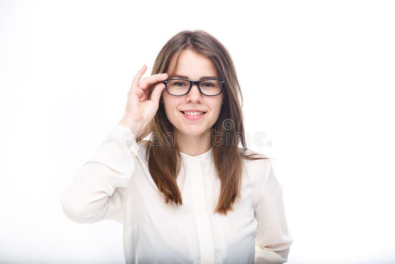 Piękna młoda dziewczyna w szkłach z czarnym obręczem biała koszula na odosobnionym tle pojęcia prowadzenia domu posiadanie klucza zdjęcia royalty free