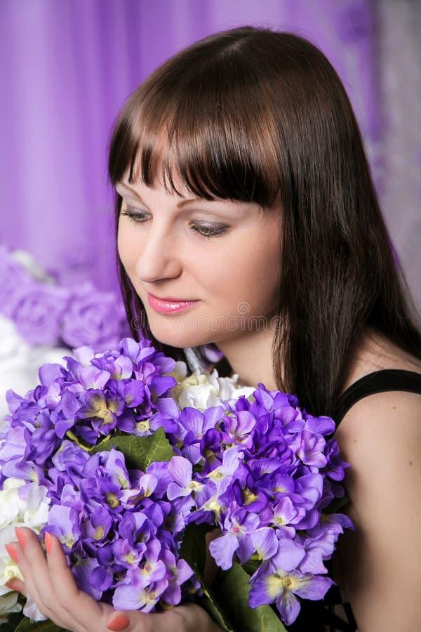 Piękna młoda dziewczyna z bukietem purpurowi kwiaty zdjęcia stock