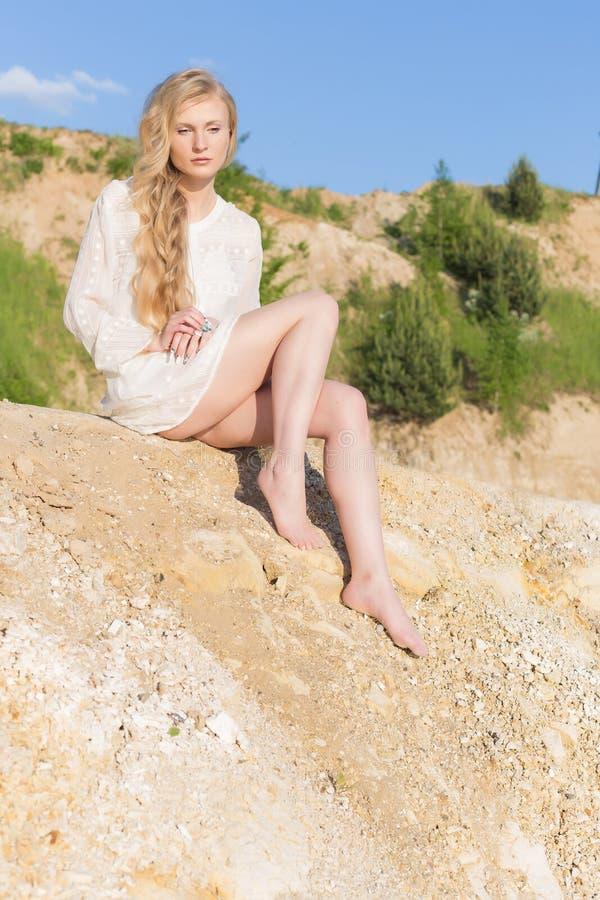 Piękna młoda dziewczyna z długim blondynem w białym smokingowym obsiadaniu na plaży jezioro na jaskrawym słonecznym dniu zdjęcia royalty free