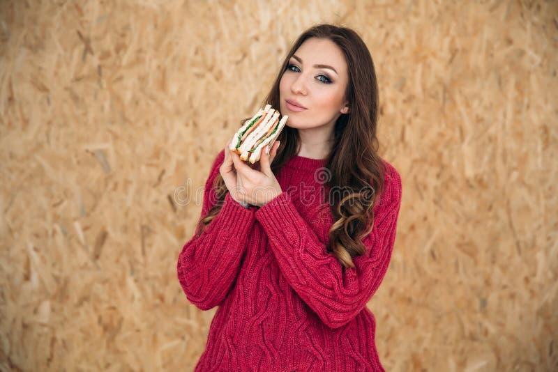 Piękna młoda dziewczyna z dużymi zielonymi oczami w jaskrawym codziennym pulowerze chce jeść jej wyśmienicie jarską kanapkę obraz royalty free