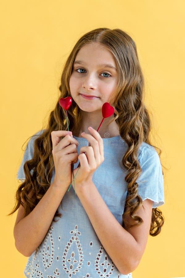 Piękna młoda dziewczyna z dwa sercami w jej rękach Pojęcie walentynki ` s dzień Żółty tło obraz stock