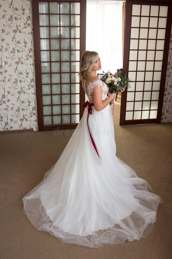 Piękna młoda dziewczyna z stojakami w lobby hotel w ślubnej sukni z ślubnym bukietem w ona i makijażu i uczesania obrazy stock