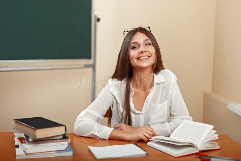 Piękna młoda dziewczyna z uśmiechem, siedzi na szkolnym biurku z fotografia stock