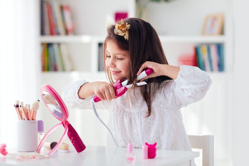 Piękna, młoda dziewczynka, kręcąca włosy żelaznym curlerem i kompletem piękności zabawek zdjęcie royalty free