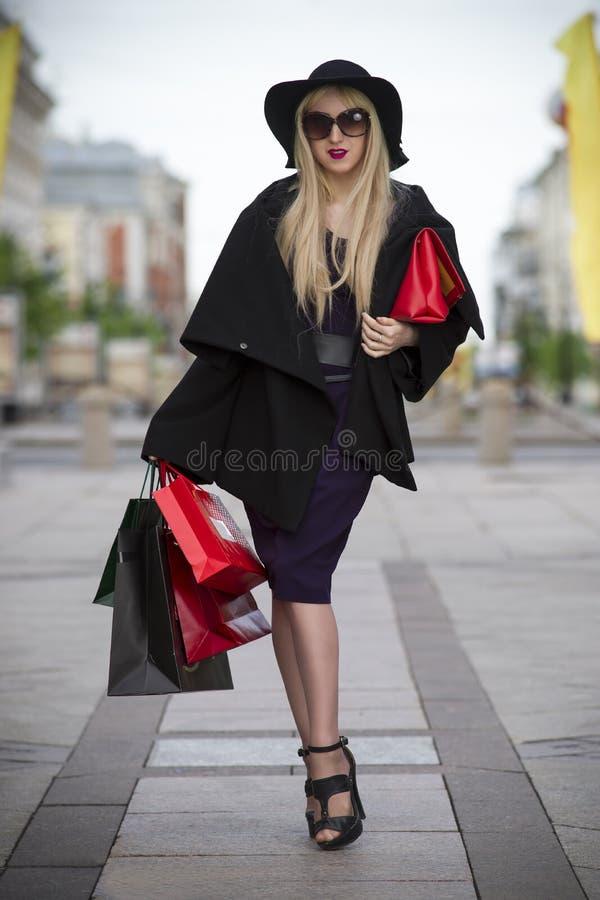 Piękna młoda elegancka blondynki kobieta w sukni, żakiecie, okularach przeciwsłonecznych i kapeluszu z torba na zakupy błękita, c zdjęcia royalty free