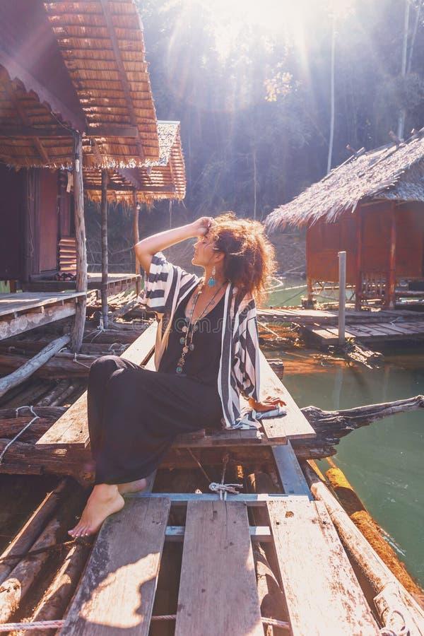 Piękna młoda elegancka boho kobieta przy drewnianą spławową wioską fotografia royalty free
