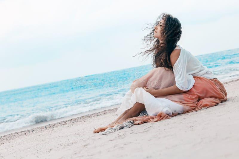 Piękna młoda elegancka kobieta w menchiach omija na plaży obraz royalty free