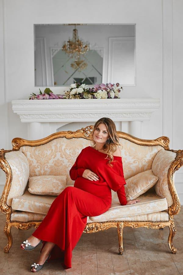 Pi?kna m?oda gestation kobieta w modnej czerwonej wiecz?r sukni siedzi na z?ocistej rocznik le?ance przy luksusowym wn?trzem zdjęcie royalty free