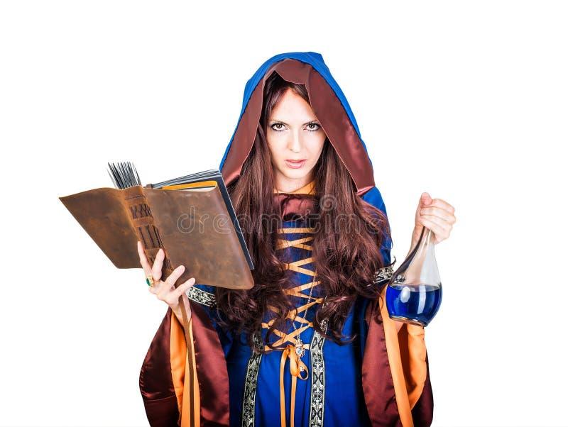 Piękna młoda Halloween czarownica czyta magiczną książkę i trzymać obraz stock