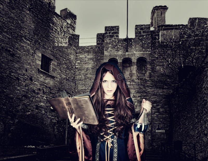 Piękna młoda Halloween czarownica czyta magiczną książkę i trzymać obrazy stock