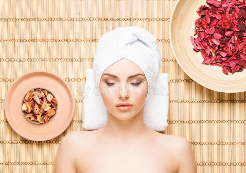 Piękna, młoda i zdrowa kobieta w zdroju salonie na bambus macie, S zdjęcie stock