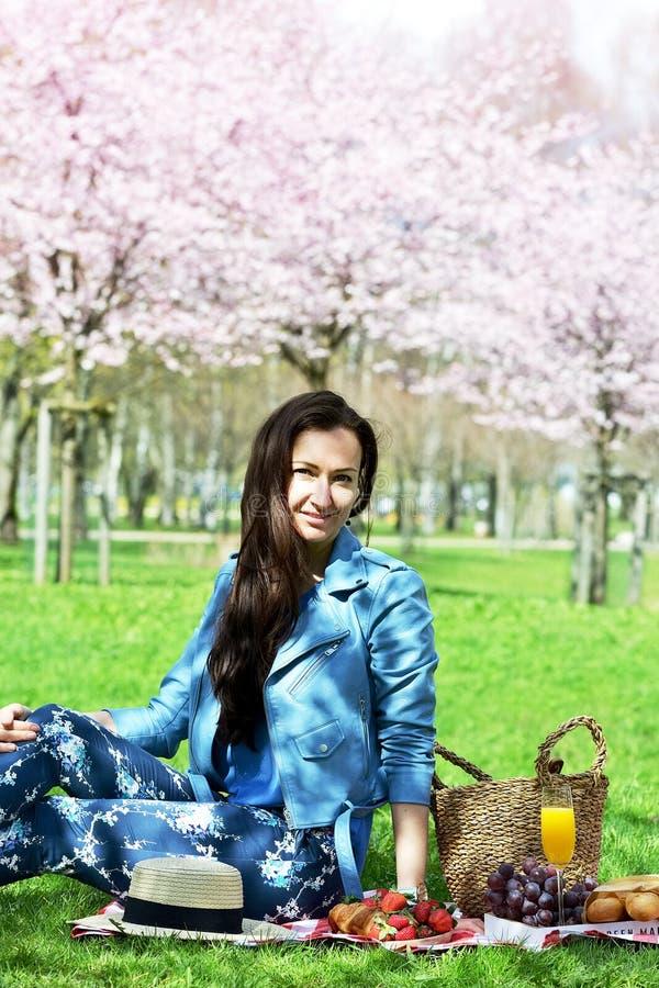 Piękna Młoda Kaukaska kobieta w Błękitnej skórzanej kurtce Ma pinkin w parku zdjęcie stock