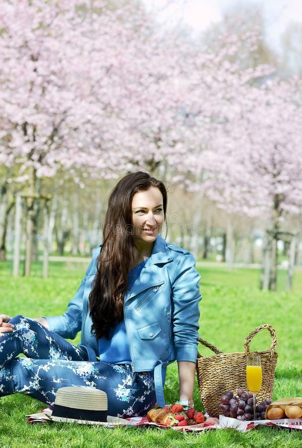 Piękna Młoda Kaukaska kobieta w Błękitnej skórzanej kurtce Ma pinkin w parku obraz stock