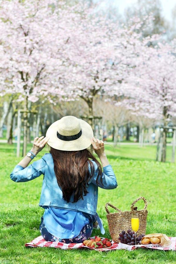 Piękna Młoda Kaukaska kobieta w Błękitnej skórzanej kurtce Ma pinkin w parku fotografia stock