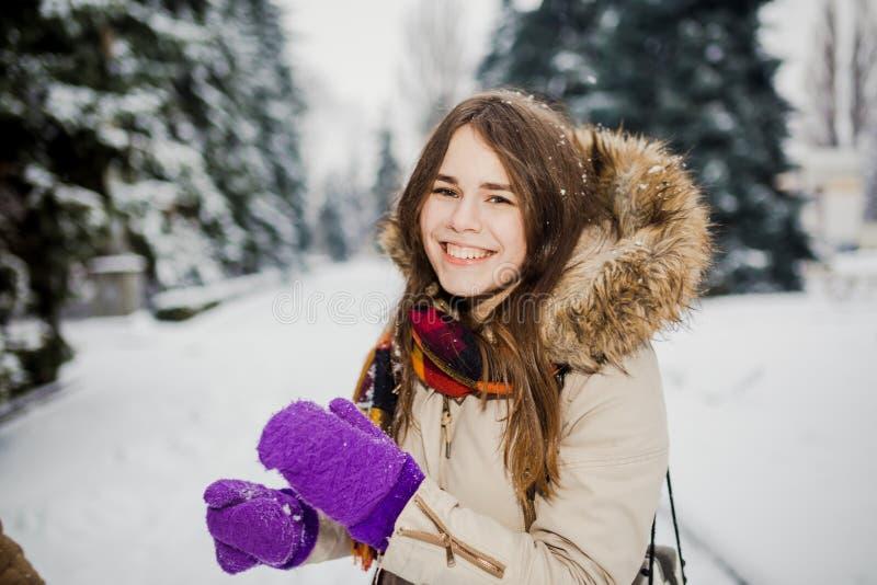 Piękna młoda Kaukaska kobiety radości szczęścia uśmiechu sztuka z śniegiem blisko iglastego drzewa w śnieżnym parku zdjęcie stock